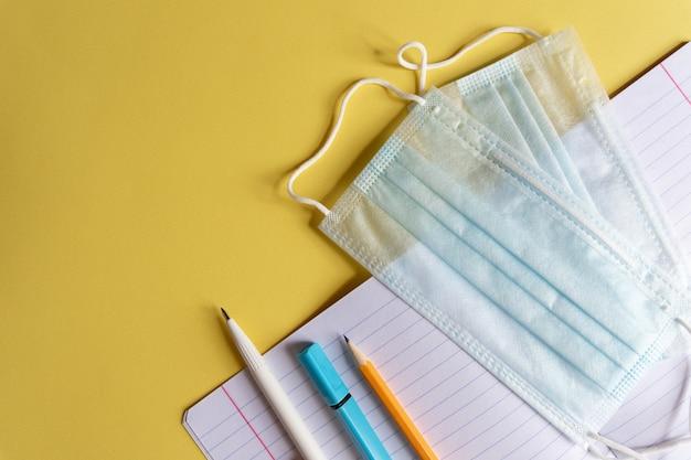 Máscara protetora, gel desinfetante e material escolar em fundo amarelo