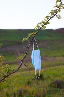 Máscara protetora médica na árvore, poluição ambiental.