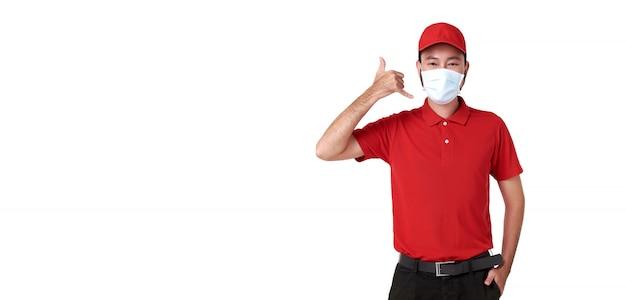 Máscara protetora vestindo asiática do homem de entrega no uniforme vermelho e em fazer o gesto da chamada isolado sobre o fundo branco.