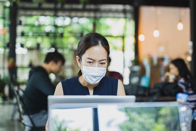 Máscara protetora vestindo da mulher de negócio asiática que trabalha no portátil.