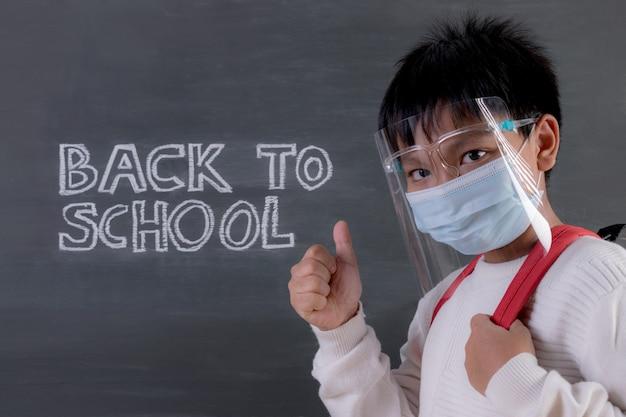 Máscara protetora vestindo do menino de escola que está contra o quadro-negro com texto. de volta à escola durante covid-19.