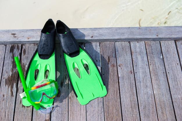 Máscara, snorkel e nadadeiras para mergulho no molhe de madeira
