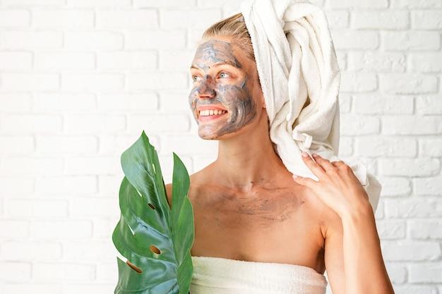 Máscara spa facial. spa e beleza. mulher feliz e sorridente usando toalhas de banho e uma máscara facial de argila no rosto, segurando uma folha verde de monstera