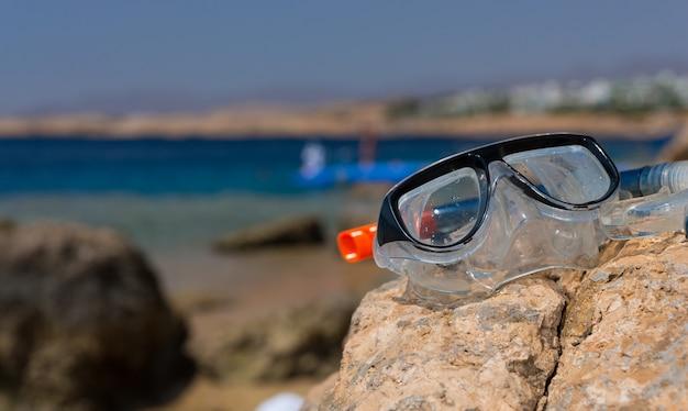 Máscara subaquática e tubo deitado na rocha na praia em um dia ensolarado de verão, bela vista do mar ao fundo