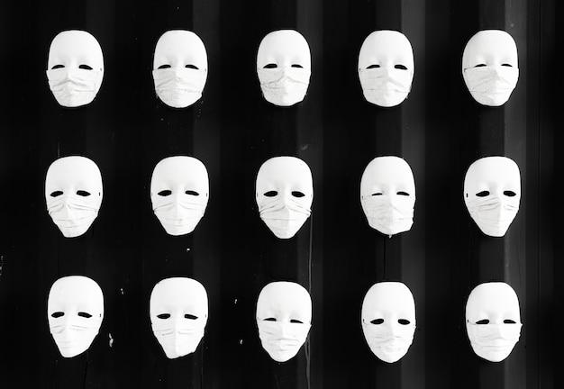 Máscara usando máscara cirúrgica com fundo preto na parede