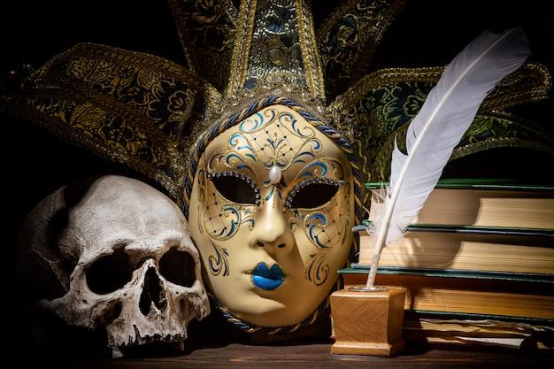 Máscara veneziana com tinteiro antigo, penas, pena, livros e crânio na mesa de madeira.