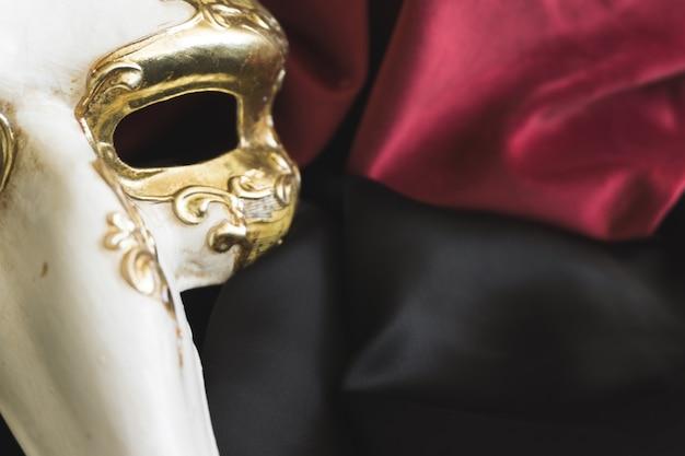 Máscara veneziana com um longo nariz em um tecido preto fechar-se