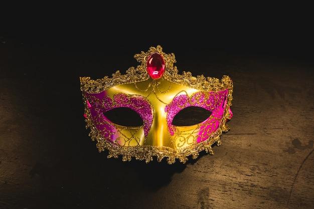 Máscara veneziana dourada em uma mesa de madeira