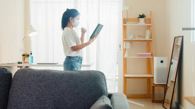 Máscara vestindo asiática da mulher de negócio usando a videoconferência da chamada de funcionamento da tabuleta com o cliente na sala de visitas da casa quando o distanciamento social fica em casa e o tempo de quarentena do auto, conceito do coronavirus.