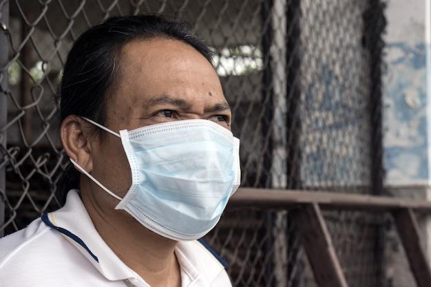 Máscara vestindo da boca do homem asiático contra a poluição do ar na fábrica.