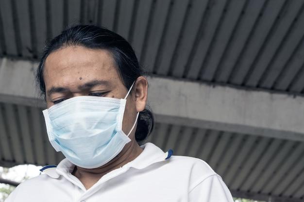 Máscara vestindo da boca do homem asiático contra a poluição do ar.