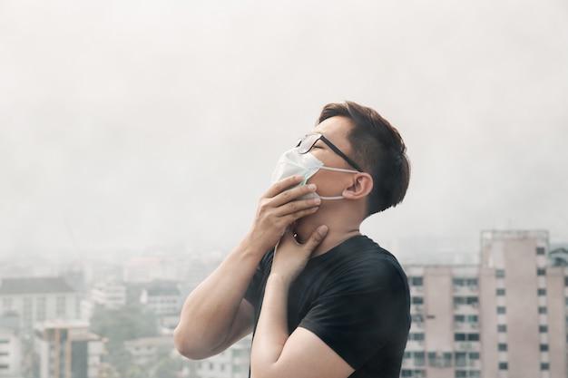 Máscara vestindo da higiene do homem asiático e doente devido à poluição do ar na cidade.