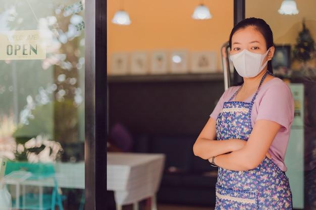 Máscara vestindo da mulher asiática que está com placa aberta do sinal na janela na cafetaria.