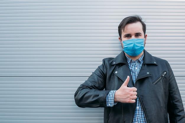 Máscara vestindo do homem que aparece o polegar. homem usa máscara protetora contra doenças infecciosas e gripe. conceito de cuidados de saúde. quarentena do coronavírus.