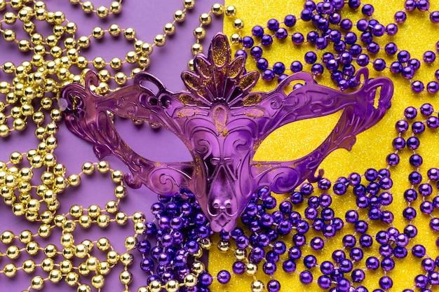 Máscara violeta e colares de pérolas