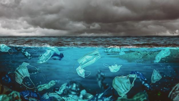 Máscaras cirúrgicas e garrafas plásticas no mar. risco ambiental na época de covid-19.