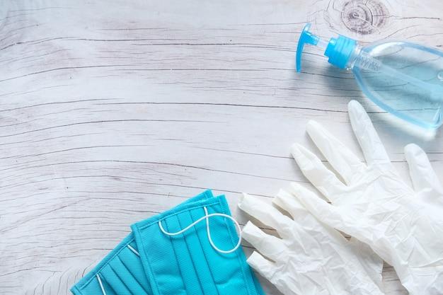 Máscaras cirúrgicas, luvas médicas e desinfetante para as mãos no fundo de madeira