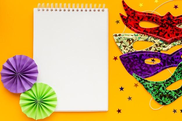 Máscaras coloridas e bloco de notas em branco
