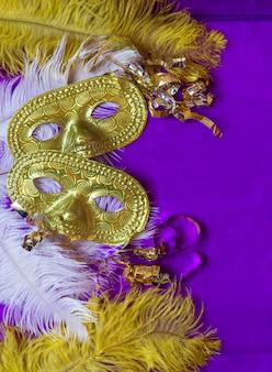 Máscaras de carnaval e penas e superfície roxa
