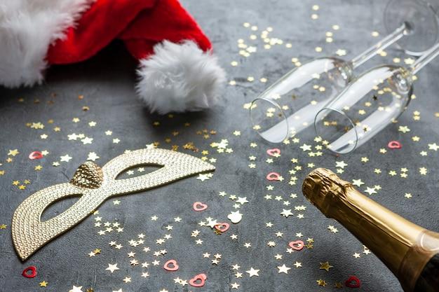 Máscaras de carnaval, garrafas de champanhe e chapéu vermelho do papai noel e duas taças de champanhe e confetes com glitter dourado,