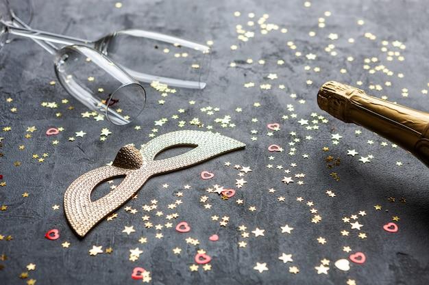 Máscaras de carnaval, garrafas de champanhe e duas taças de champanhe e confetes com glitter dourado,