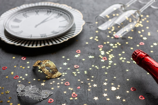 Máscaras de carnaval, garrafas de champanhe e duas taças de champanhe e confetes glitter dourados, vista superior, close-up em fundo cinza