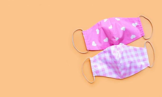 Máscaras de pano rosa artesanal sobre fundo de cor creme. copie o espaço