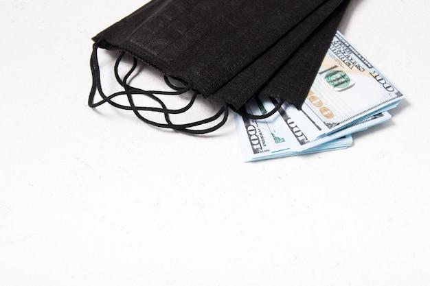 Máscaras de proteção e notas de 100 dólares em um fundo branco, copie o espaço