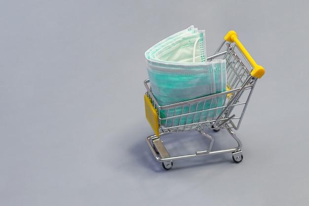 Máscaras de proteção médica bebê em um pequeno carrinho de compras, copie o espaço.