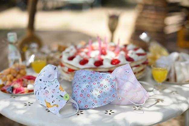 Máscaras de proteção para crianças na mesa de aniversário com bolo e doces