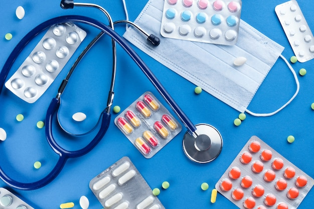 Máscaras descartáveis médicas protetoras, tabuletas e medicamentos, estetoscópio sobre um fundo azul.