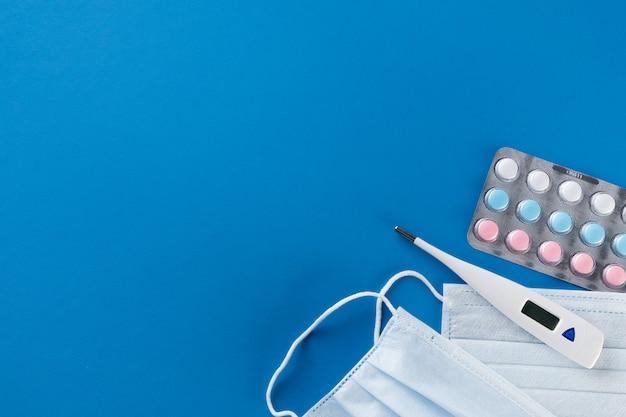 Máscaras descartáveis médicas protetoras, termômetro, comprimidos e medicamentos sobre um fundo azul.