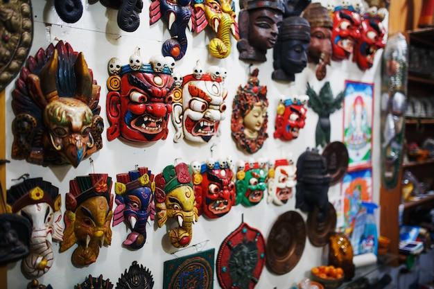 Máscaras esculpidas coloridas são vendidas, máscaras coloridas de perfumes diferentes penduradas na parede.