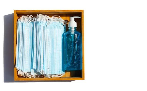 Máscaras faciais com desinfetante de gel líquido à base de álcool em caixa de madeira em superfície branca