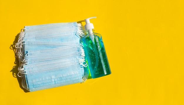 Máscaras faciais com desinfetante de gel líquido à base de álcool na superfície amarela