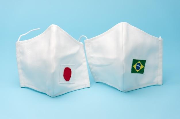 Máscaras faciais de tecido caseiro com a bandeira brasileira e japonesa