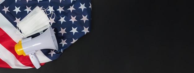 Máscaras faciais e megafone com a bandeira dos estados unidos da américa (eua) em fundo preto.