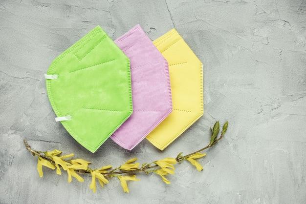 Máscaras faciais verdes, rosa e amarelas com flores amarelas sobre fundo de concreto