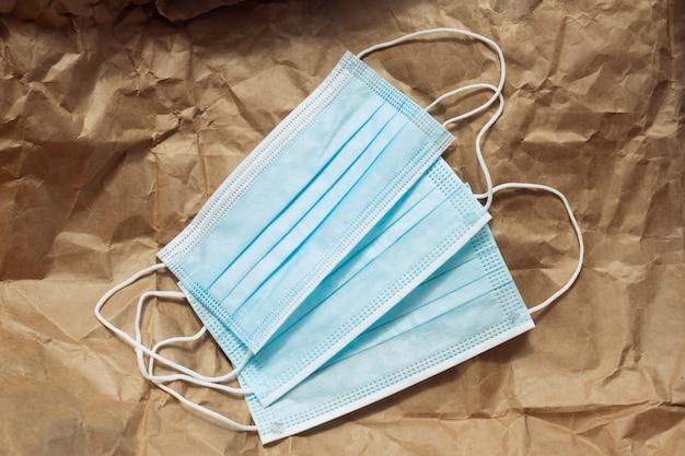 Máscaras médicas antibacterianas azuis em papel ofício.