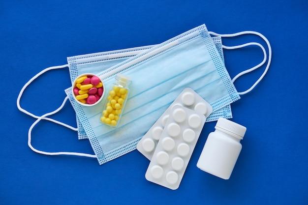 Máscaras médicas com pílulas diferentes sobre um fundo azul