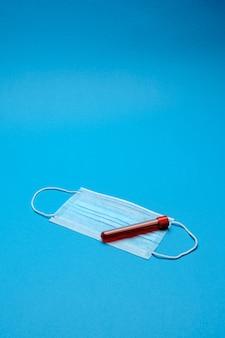 Máscaras médicas de proteção e tubo de ensaio com amostra de sangue em azul com