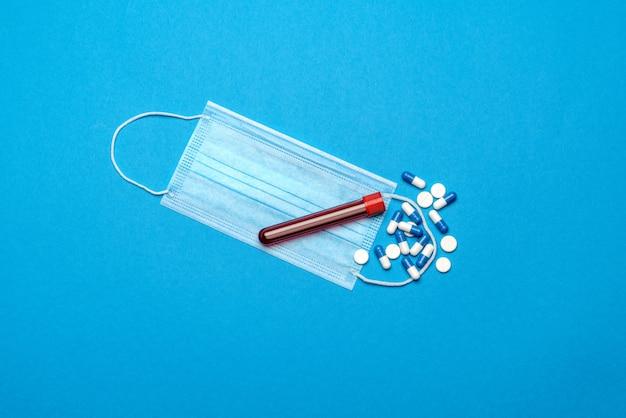 Máscaras médicas de proteção, tubo de ensaio com amostra de sangue e comprimidos