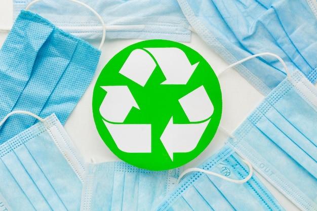 Máscaras médicas descartáveis de vista superior e símbolo de reciclagem