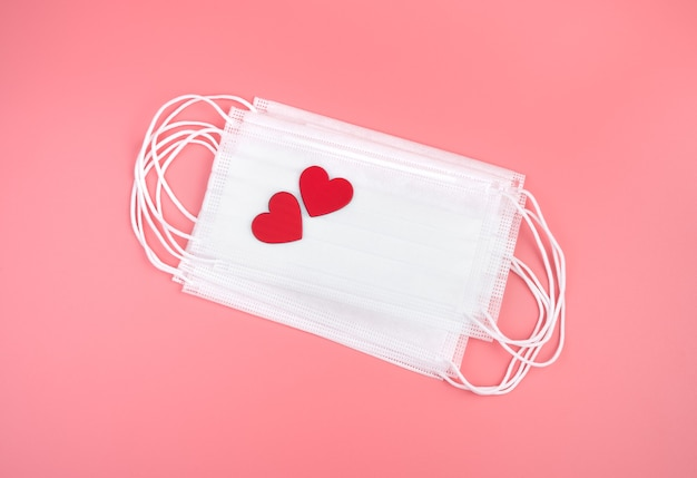 Máscaras médicas e dois corações em um fundo rosa. vista de cima, com espaço para copiar. conceito 14 de fevereiro.