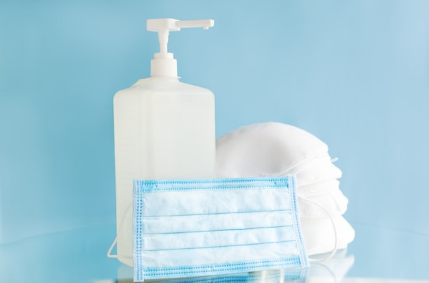 Máscaras médicas médicas, máscara protetora cirúrgica n95 e frasco de gel de álcool para higienizar as mãos sobre fundo azul. prevenção de vírus covid 19 de coronavírus