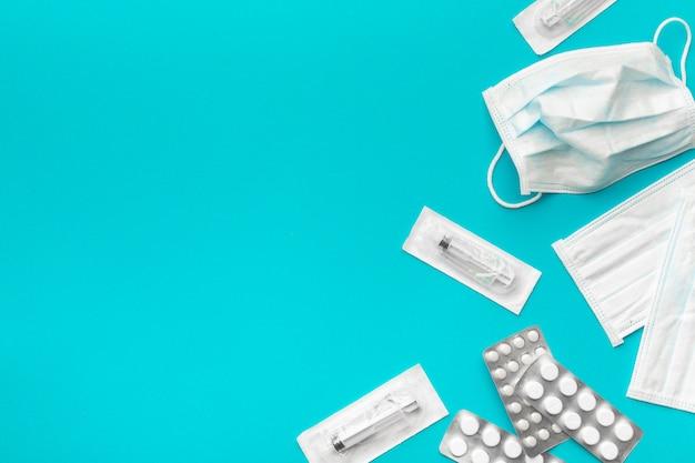 Máscaras protetoras médicas, seringa descartável em embalagens estéreis e embalagens farmacêuticas com comprimidos no papel, fundo azul brilhante. o conceito de proteger a saúde do vírus. copie o espaço