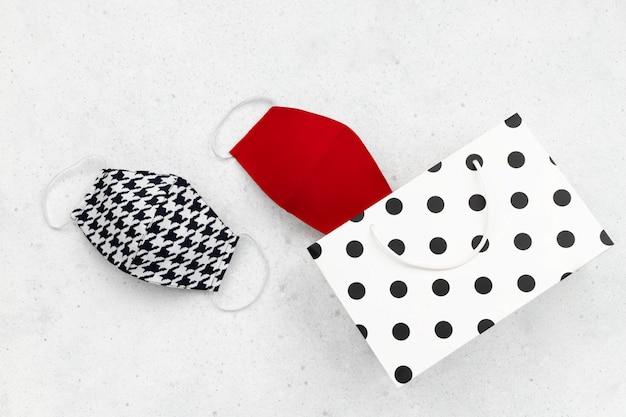 Máscaras protetoras na moda femininas com sacola de compras na mesa cinza. vista plana leiga nova composição normal.