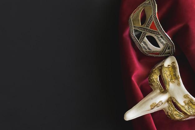 Máscaras venezianas em uma tela preta e vermelha