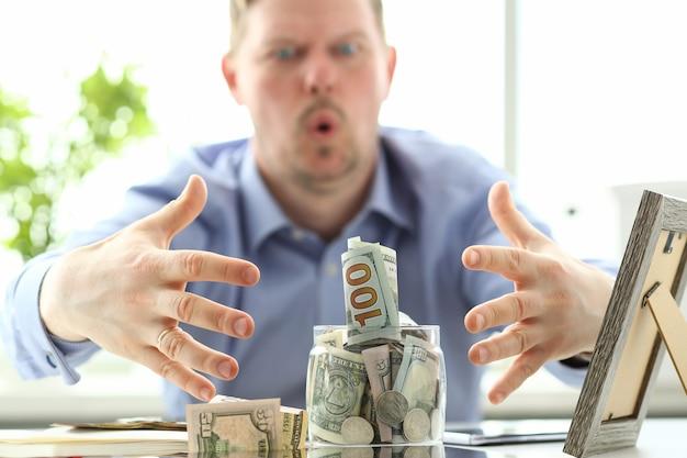 Masculinas mãos agarrando grande frasco gordo cheio de moeda dos eua como gesto de ganância