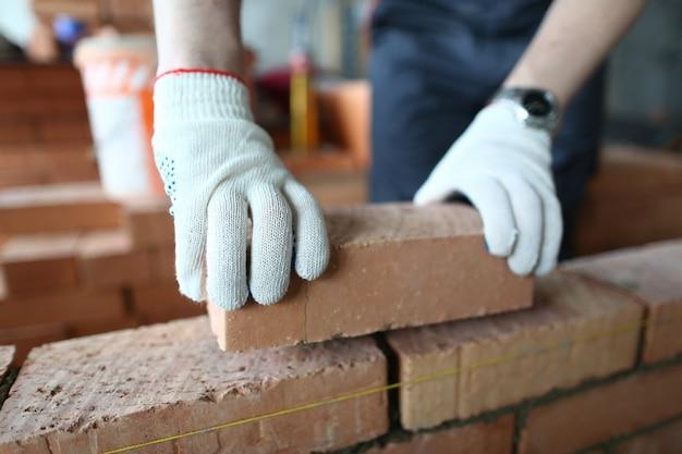 Masculinas mãos colocando tijolo
